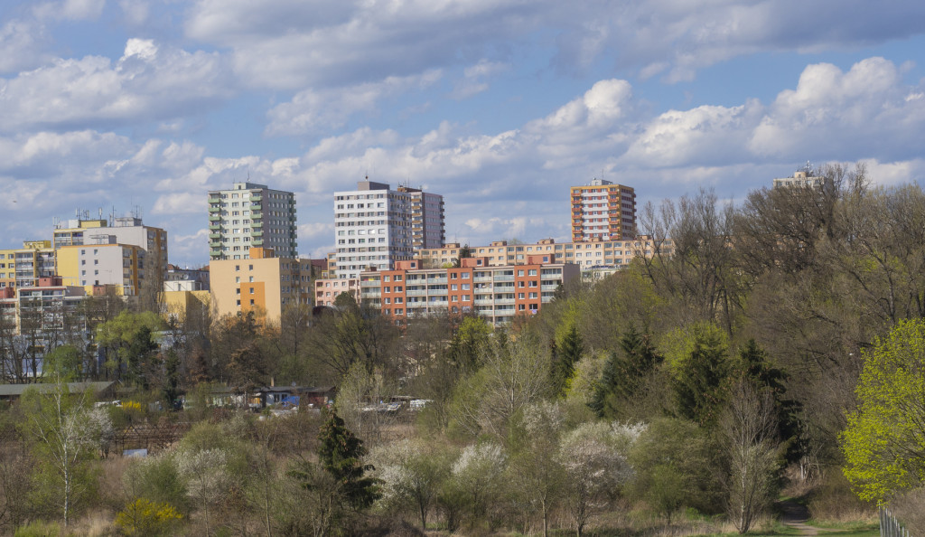 early spring  Prague landscape with high-rise apartment building, brown field, green grass, trees with fresh lush leaves and blue sky, white fluffy clouds backgroud, copy space, vivid colors